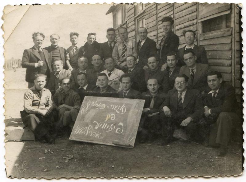 La chorale du camp de Pithiviers, en avril 1942. Chaïm Goldsztajn est le 1er à gauche, assis au 2e rang. Même rangée, Mendel Zemelman, auteur du chant de Pithiviers, est le 4e (en blanc), à côté d'Ojzer Kawka (avec les lunettes). Archives familiales
