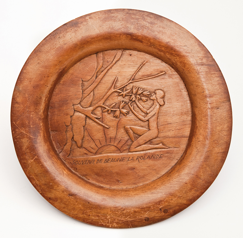 Assiette de bois gravé en relief représentant une femme nue agenouillée au pied d'un arbre. Bois gravé. Dimensions 24 x 2 cm. Objet fabriqué par Szmul Jeger dans le camp de Beaune-La-Rolande (entre mai 1941 et juin 1942, sd). Inscription « SOUVENIR DE BEAUNE LA ROLANDE ». Collection familiale – Photo © Géraldine Aresteanu