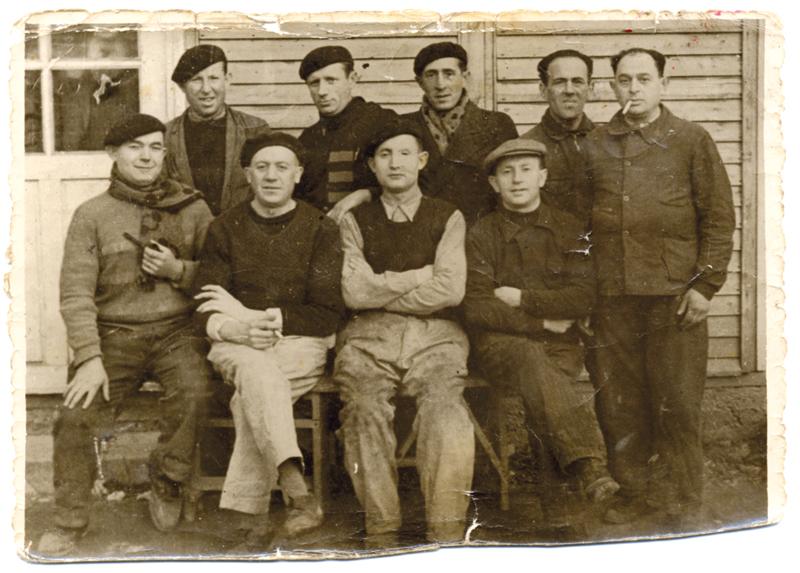 """Au camp de Beaune-la-Rolande. Bernard (Bencjan) Wajsman est debout, au milieu de la 2e rangée. Jankiel Laznowski est à sa droite. Au 1er rang, assis, Chaïm Kac est le 2e en partant de la gauche (13 décembre 1941) Inscription au verso: """"Souvenir de / Beaune-la-Rolande / le 13 décembre mil neuf cent / quarante et un jusea / Bernard"""". Archives familiales"""