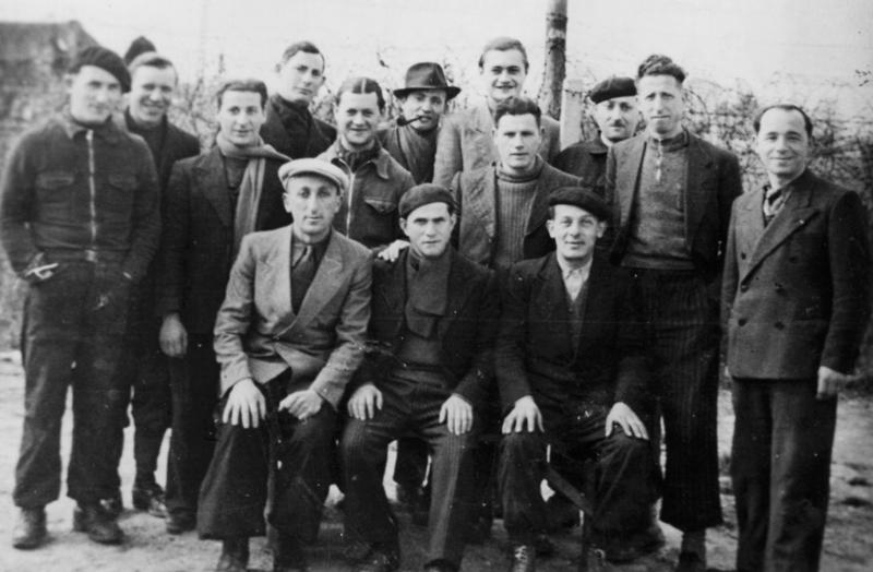 Au camp de Beaune-la-Rolande. Judko Mandelcwajg est au 2e rang, le 2e en partant de la gauche, avec l'écharpe (entre mai 1941 et juin 1942, sd). Inscription au verso: «à Mes / Chers Femme / et enfants / Beaune la Rolande / le 2 avril 1942 / Mandelcwajg». Archives familiales