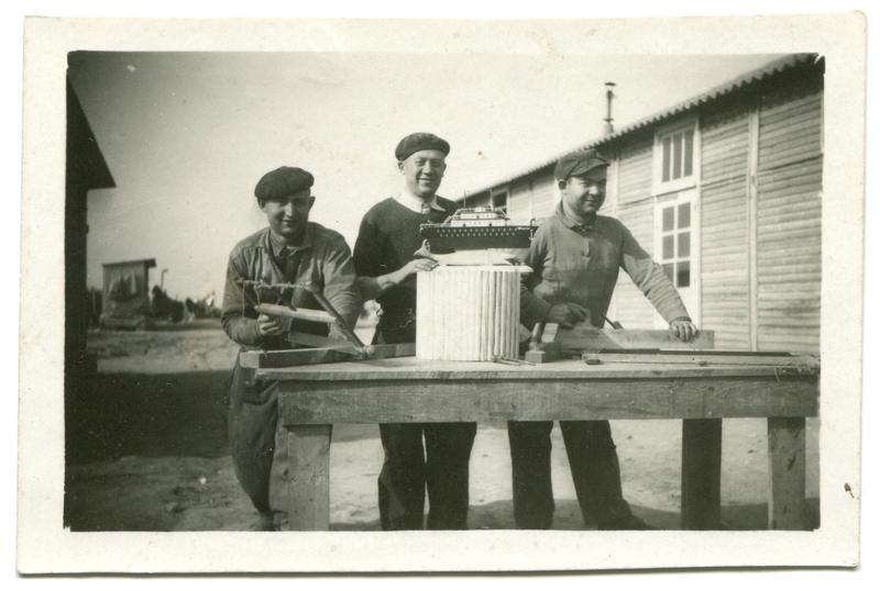 Chaïm Kac, au centre, au camp de Beaune-la-Rolande, avec le bateau qu'il vient de fabriquer pour l'une de ses deux filles (18 mai 1942). Archives Germaine Kac-Mélikian