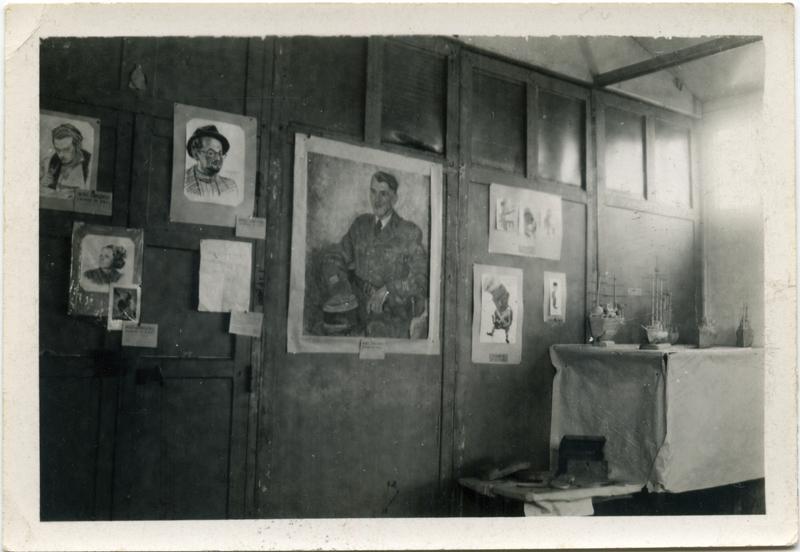 Photographie prise lors d'une exposition organisée dans le camp de Pithiviers par la commission culturelle (décembre 1941?, sd). On y voit le portrait de Zwilen Bezpalczik sous les traits du personnage de Menachem Mendel, dessiné par Franz Reisz (à gauche du grand portrait du commandant du camp). Archives familiales