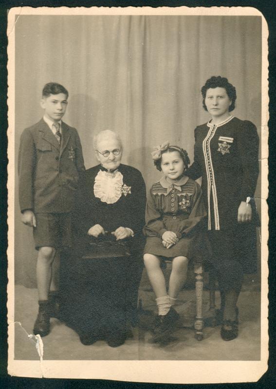 Léon et Denise Sas, avec leur grand-mère maternelle Chaya-Pessel Lubliner et leur mère Tyla, posant chez le photographe avec leur étoile jaune (juin 1942?, sd). Archives familiales